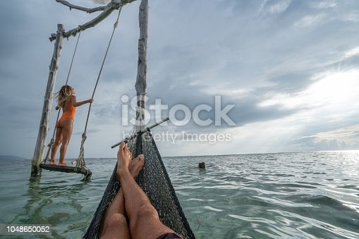 1056198278 istock photo Young couple swinging on the beach by the sea, beautiful and idyllic landscape. People travel romance vacations concept. Personal perspective of man on sea hammock and girlfriend on sea swing. 1048650052