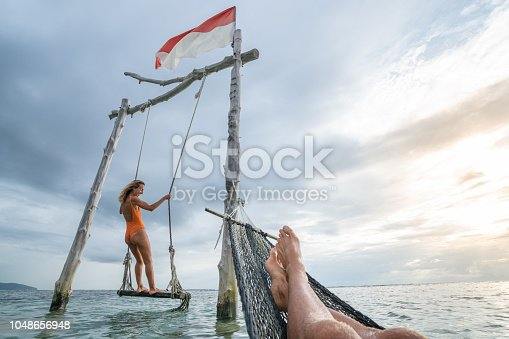 1056198278 istock photo Young couple swinging on the beach by the sea, beautiful and idyllic landscape. People travel romance vacations concept. Personal perspective of man on sea hammock and girlfriend on sea swing. 1048656948