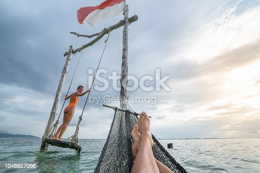 1056198278 istock photo Young couple swinging on the beach by the sea, beautiful and idyllic landscape. People travel romance vacations concept. Personal perspective of man on sea hammock and girlfriend on sea swing. 1048657056