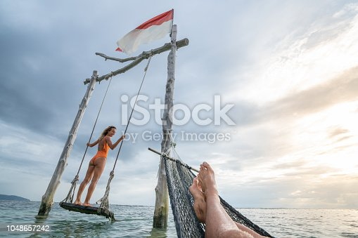1056198278 istock photo Young couple swinging on the beach by the sea, beautiful and idyllic landscape. People travel romance vacations concept. Personal perspective of man on sea hammock and girlfriend on sea swing. 1048657242