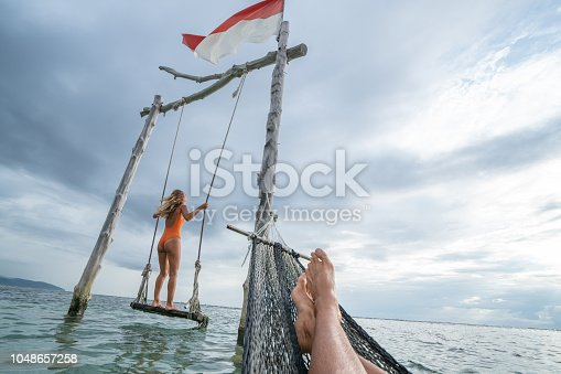 1056198278 istock photo Young couple swinging on the beach by the sea, beautiful and idyllic landscape. People travel romance vacations concept. Personal perspective of man on sea hammock and girlfriend on sea swing. 1048657258