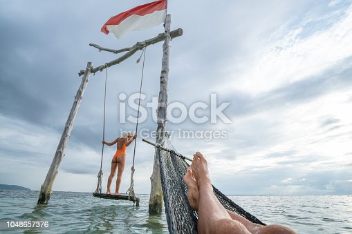 1056198278 istock photo Young couple swinging on the beach by the sea, beautiful and idyllic landscape. People travel romance vacations concept. Personal perspective of man on sea hammock and girlfriend on sea swing. 1048657376