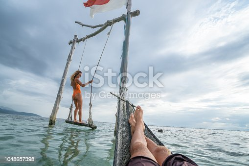 1056198278 istock photo Young couple swinging on the beach by the sea, beautiful and idyllic landscape. People travel romance vacations concept. Personal perspective of man on sea hammock and girlfriend on sea swing. 1048657398