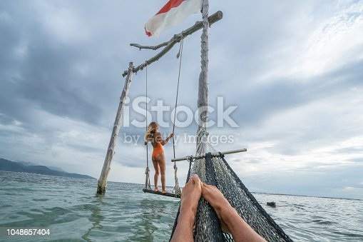 1056198278 istock photo Young couple swinging on the beach by the sea, beautiful and idyllic landscape. People travel romance vacations concept. Personal perspective of man on sea hammock and girlfriend on sea swing. 1048657404