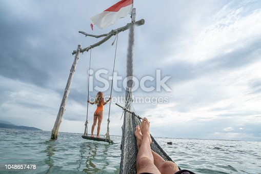 1056198278 istock photo Young couple swinging on the beach by the sea, beautiful and idyllic landscape. People travel romance vacations concept. Personal perspective of man on sea hammock and girlfriend on sea swing. 1048657478