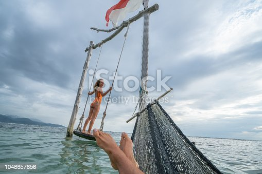 1056198278 istock photo Young couple swinging on the beach by the sea, beautiful and idyllic landscape. People travel romance vacations concept. Personal perspective of man on sea hammock and girlfriend on sea swing. 1048657656