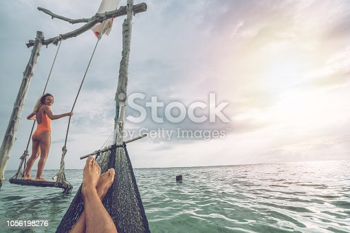1056198278 istock photo Young couple swinging on the beach by the sea, beautiful and idyllic landscape. People travel romance vacations concept. Personal perspective of man on sea hammock and girlfriend on sea swing. 1056198276