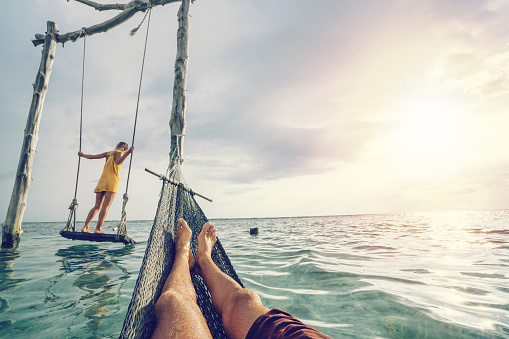 Young couple swinging on the beach by the sea, beautiful and idyllic landscape. People travel romance vacations concept. Personal perspective of man on sea hammock and girlfriend on sea swing.