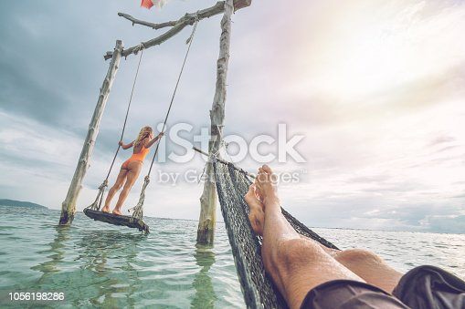 1056198278 istock photo Young couple swinging on the beach by the sea, beautiful and idyllic landscape. People travel romance vacations concept. Personal perspective of man on sea hammock and girlfriend on sea swing. 1056198286