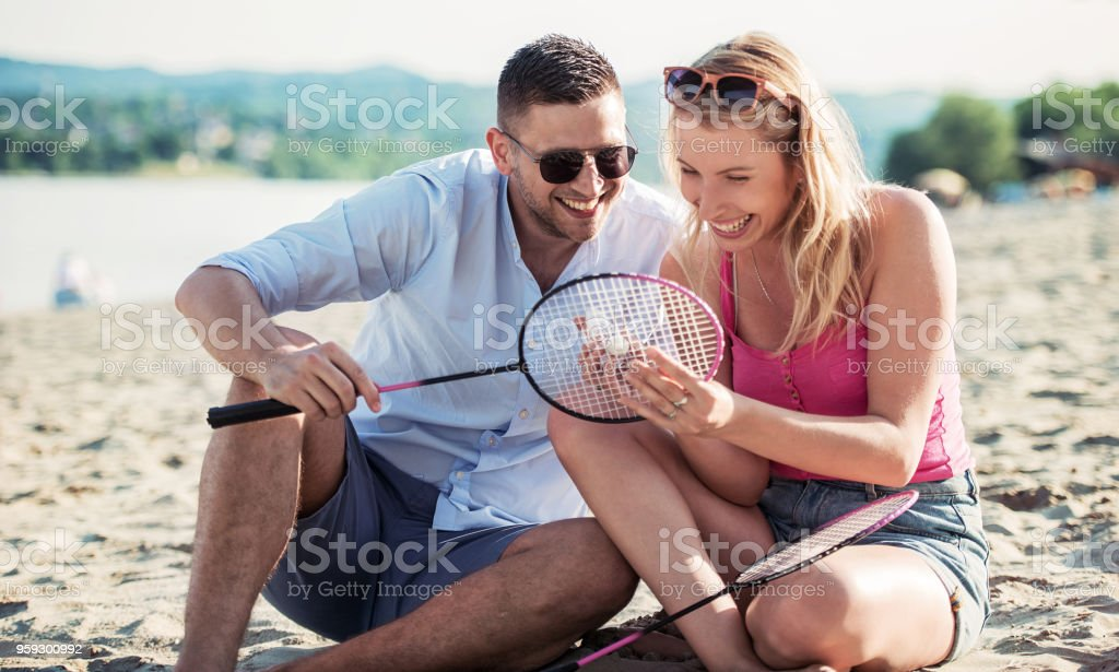 Young couple take a rest after badminton game on the summer beach. Lifestyle, love, dating, vacation concept stock photo