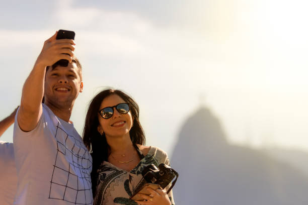 Young couple take a selfie with a smartphone on the Sugarloaf hill during sunset. Behind them is the silhouette of the Christ the Redeemer statue on the Corcovado hill stock photo