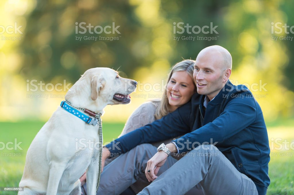 Young couple take a summer stroll with their dog on a beautiful sunny day stock photo