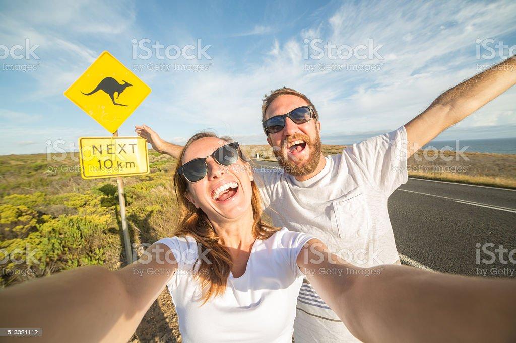 若いカップルの肖像画を近くの自分撮り警告標識-オーストラリアのカンガルー ストックフォト