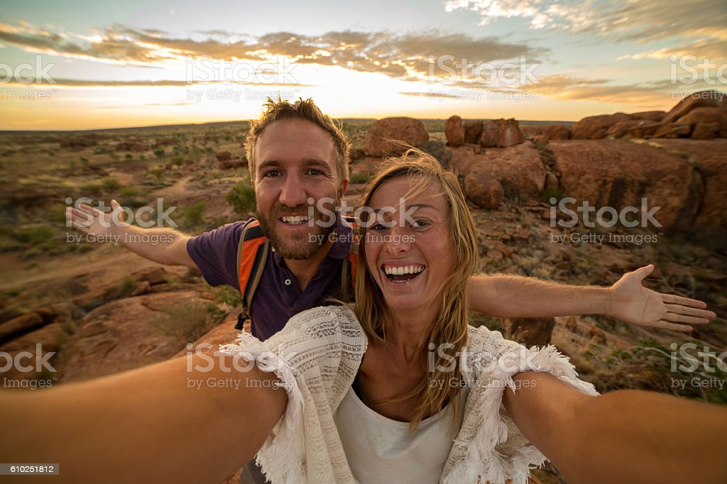 Young couple take selfie portrait with spectacular landscape at sunrise stock photo