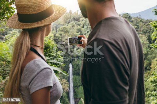 Rear view shot of couple together photographing a waterfall with mobile phone camera. Young couple taking a picture of water fall in the forest.