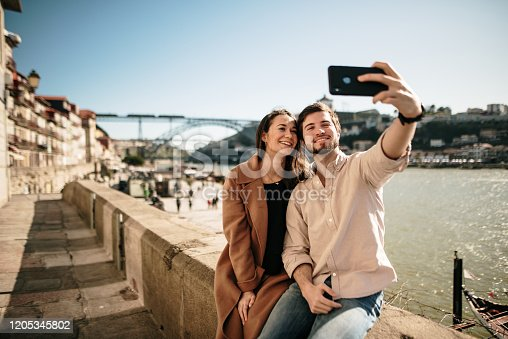 A young couple taking a selfie picture with a modern smartphone. The beautiful river side of Porto, Portugal, appears in the background. Porto is the 2nd city in Portugal and a main touristic destination in the country.