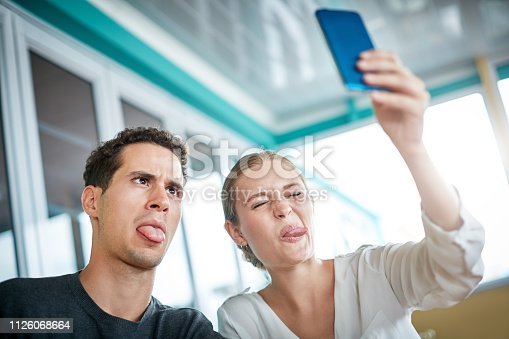 Playful young couple take  selfie with a mobile phone whilst pulling faces and sticking out their tongues.