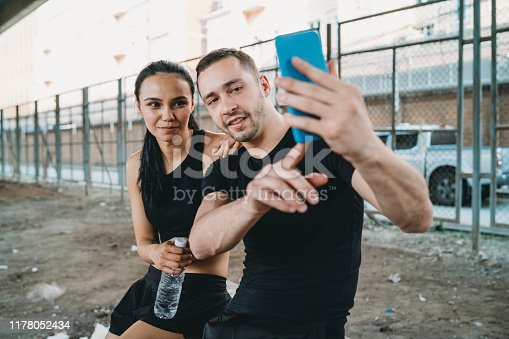 Young couple taking a selfie together during a session of training. Bangkok, Thailand