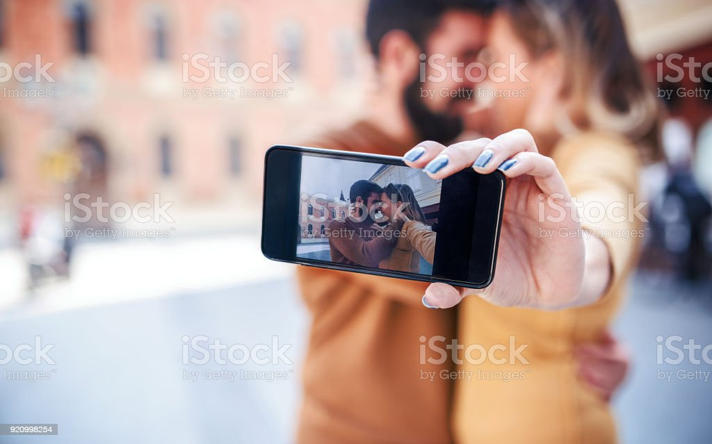 Young couple taking a selfie with mobile phone. Love and tenderness. Dating, lifestyle concept stock photo