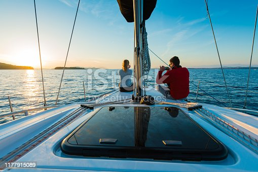 Young couple taking photos with smart phone on sailboat at sunset Taken by Sony a7R II, 42 Mpix.