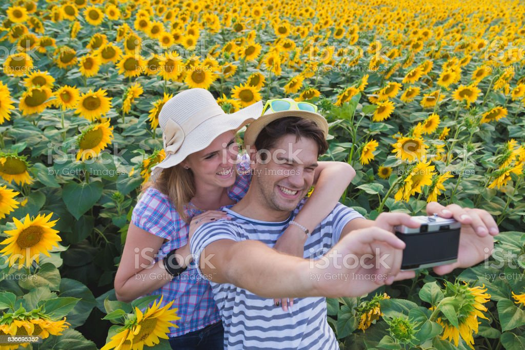 Young couple taking photos in sunflower field