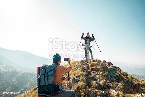 Close up of a young couple celebrating getting to the top of the mountain