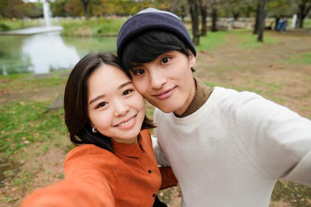 公園で自分撮りを取る若いカップル - カップル ストックフォトと画像