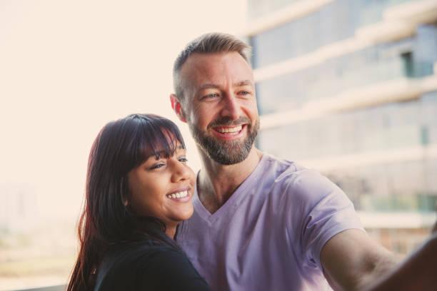 junges paar macht selfie auf dem balkon - hochzeitsreise dubai stock-fotos und bilder