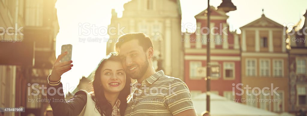 Young couple taking selfie in the city at sunset Portrait of contemporary happy young couple taking selfie using smart phone in the city at sunset. 2015 Stock Photo