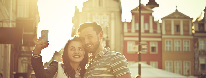 Young Couple Taking Selfie In The City At Sunset Stock Photo - Download Image Now