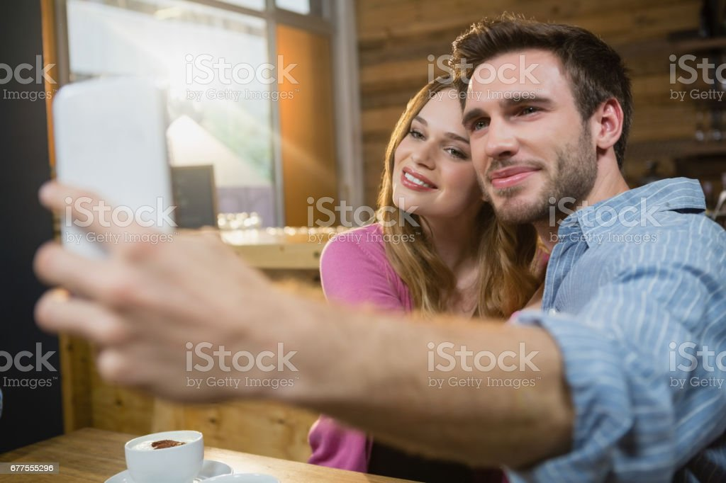 Young couple taking selfie on mobile phone while having coffee stock photo