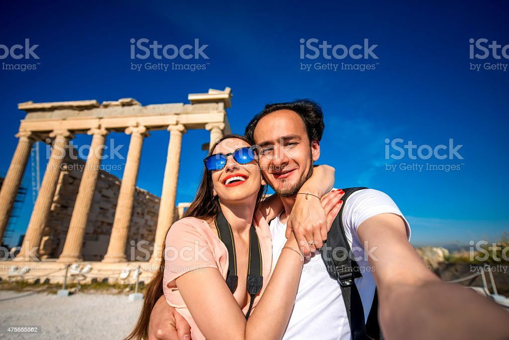 Young couple taking selfie picture with Erechtheum temple on background stock photo