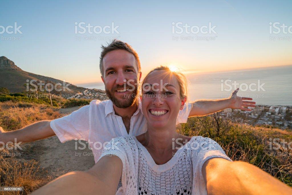 年輕的夫婦在海邊日落時採取自拍照肖像 免版稅 stock photo