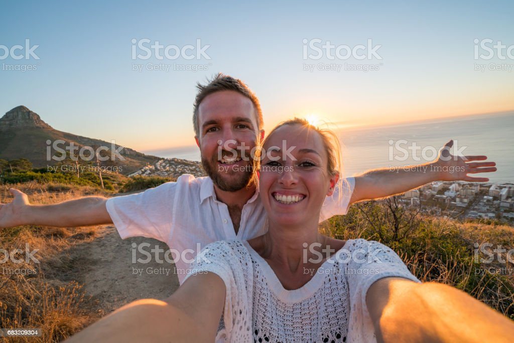Young couple taking selfie portrait by the sea at sunset foto de stock royalty-free