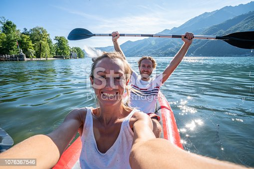 Young couple canoeing take selfie on beautiful mountain lake in Switzerland.  Inflatable red canoe on water with mountain scenery People travel outdoor activity concept
