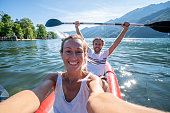 Young couple canoeing take selfie on beautiful mountain lake in Switzerland. \nInflatable red canoe on water with mountain scenery\nPeople travel outdoor activity concept