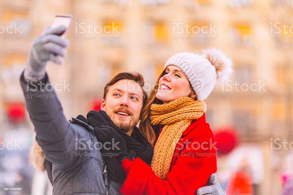 Young couple taking selfie together on a date at a public ice rink stock photo