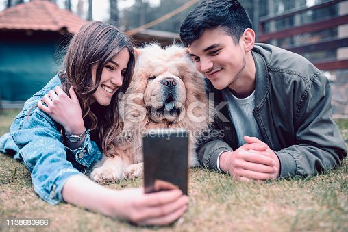 istock Young Couple Taking Selfie With Chow Dog 1138680966