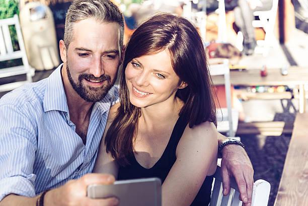 young couple taking selfie with smartphone in berlin street cafe - kvinna cloes up bildbanksfoton och bilder