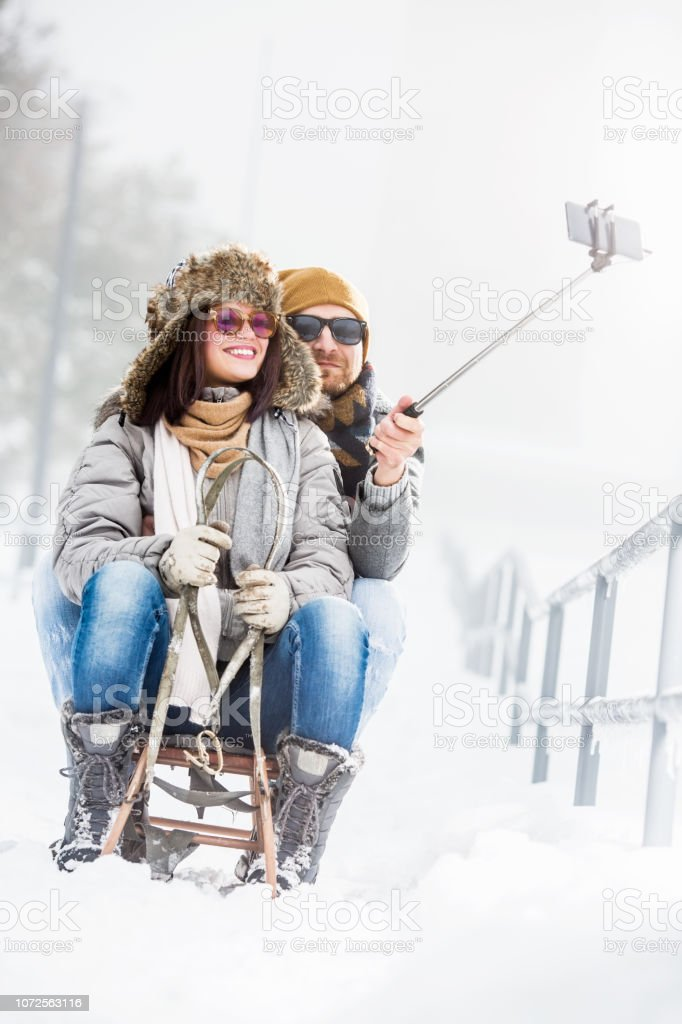 Young couple taking selfies in snow outdoors stock photo