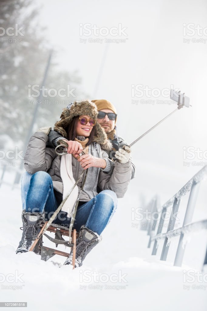 Young couple taking selfies in winter outdoors stock photo