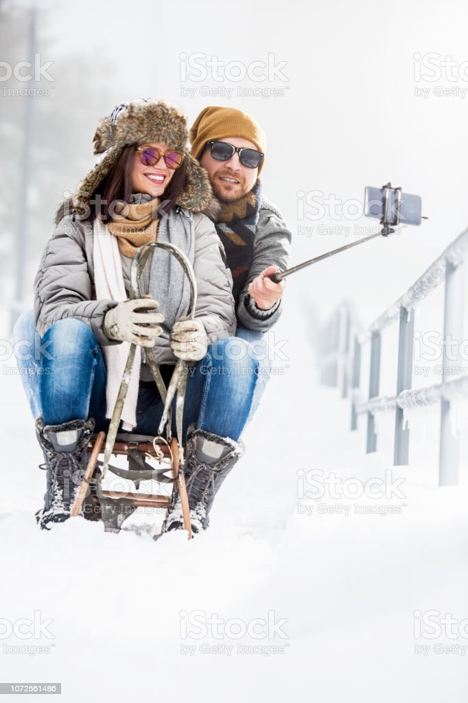 Young couple taking selfies on sledge in snow stock photo