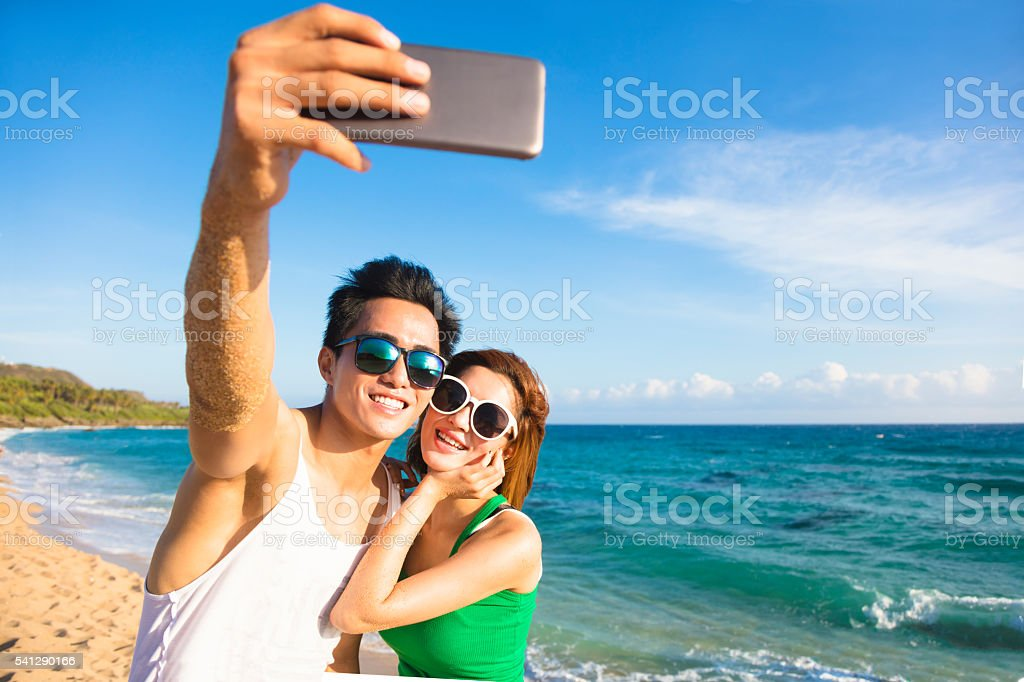 young couple  taking vacation selfie photograph at the beach  young couple  taking vacation selfie photograph at the beach - foto de acervo