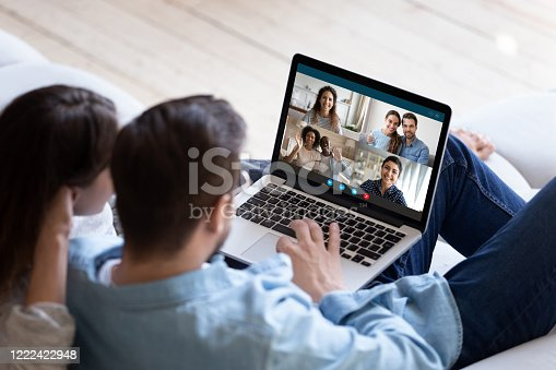 Back view of young couple relax on couch speak talk on video call with multiracial friends, man and woman spouses rest on sofa at home engaged in webcam conference conversation with relatives