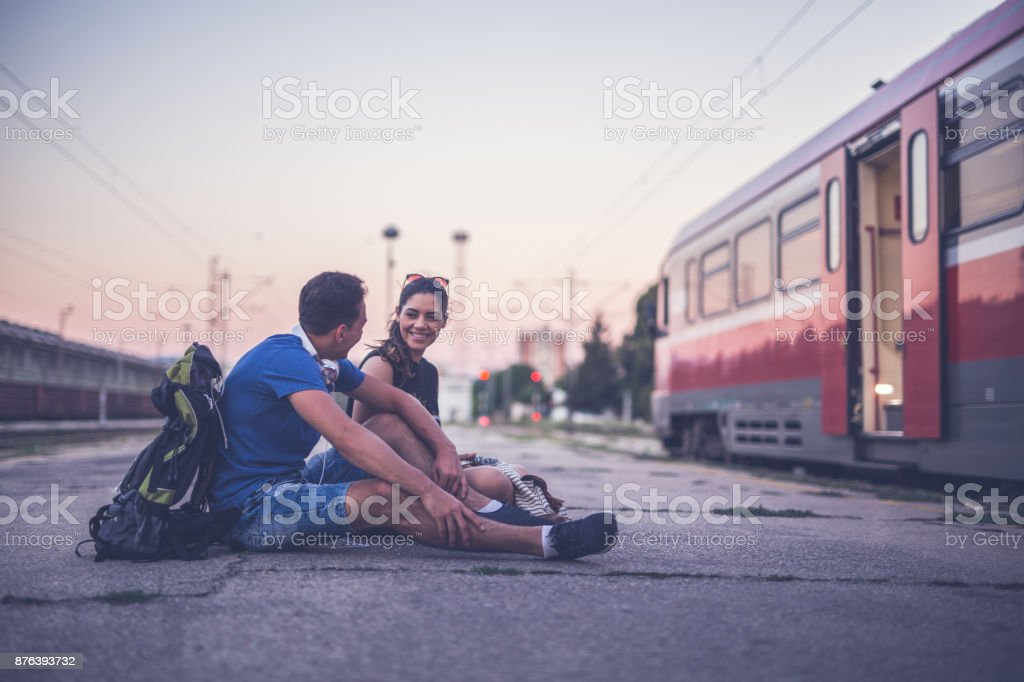 Young couple talking at railway station stock photo