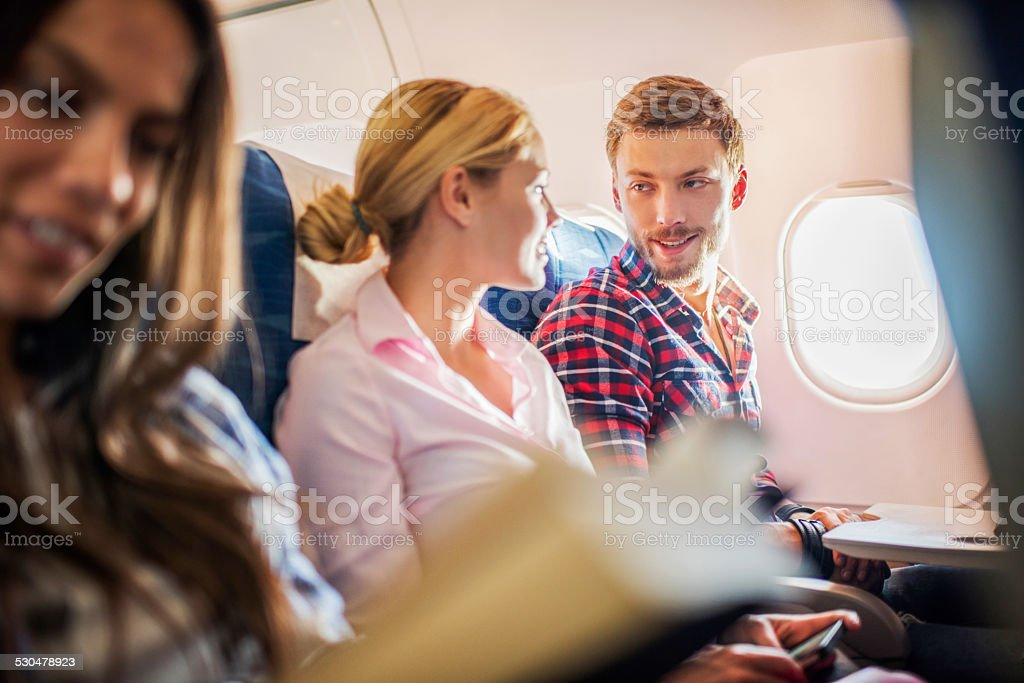 Young couple talking in airplane. stock photo