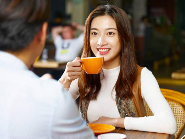 若いカップルが喫茶店で話しています。 - ガールフレンド ストックフォトと画像