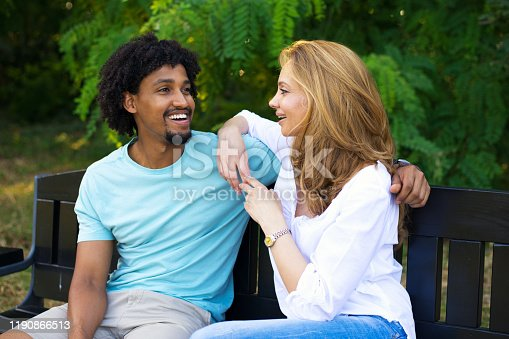 Young couple talking while sitting on the bench on a beautiful summer day.