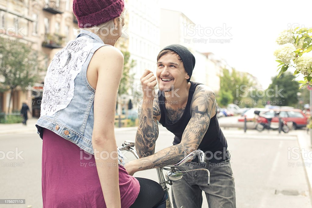 Young couple talking next to bicycle stock photo