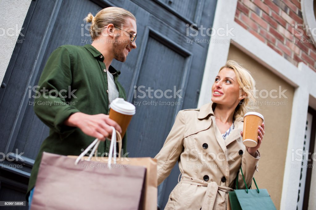 young couple talking while holding disposable coffee cups and shopping bags on street stock photo
